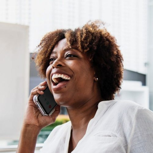 Woman in a bright white office setting laughing while talking into her cellphone.