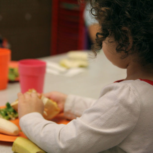 Photo of a small girl seated at a lunch table with others, eating a nutritious lunch.