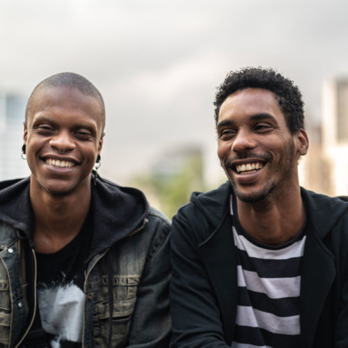 Two African-American men seated next to each other outside in front of a cityscape.