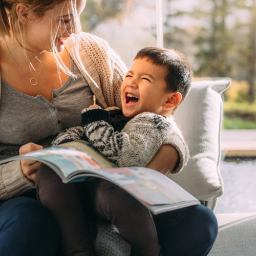 A mother holds her laughing son in her lap as she reads to him.