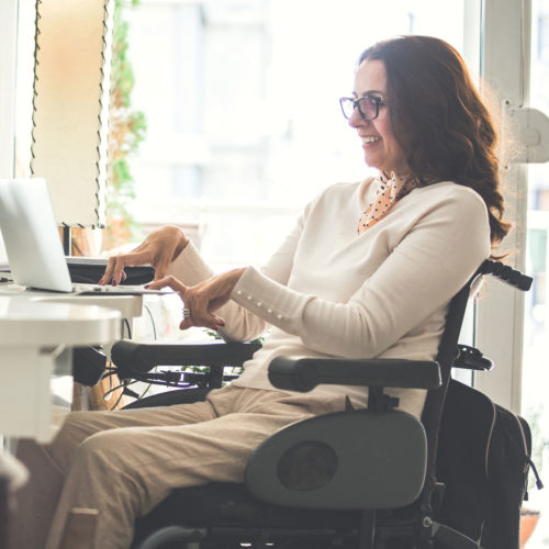 Woman seated in a wheelchair in her home office working on her laptop and smiling.