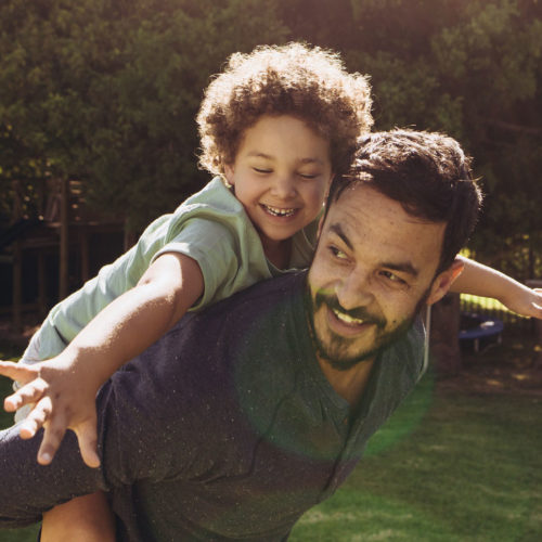 Dad gives his son a piggy-back ride outside while his son spreads his arms out wide, smiling.