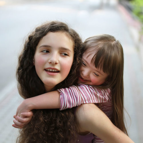 Young girl gets hugged from behind by younger girl.
