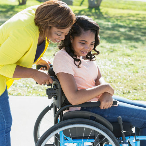 A woman leans over to listen as she pushes the wheelchair of a young woman.