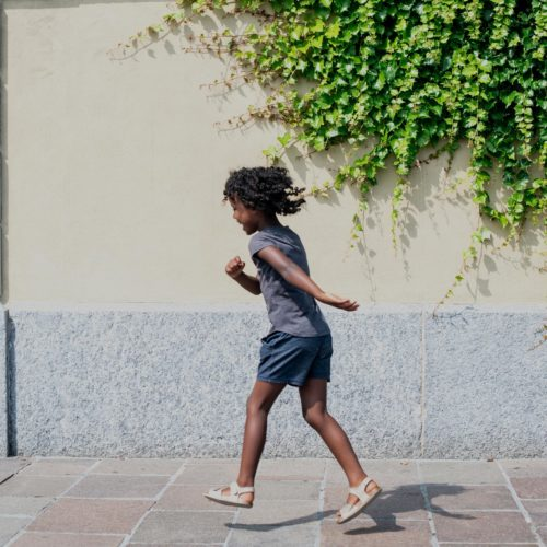 Outdoor photo of a young girl skipping away down a sidewalk with green ivy hanging down the wall.