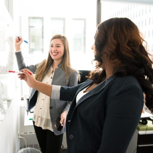 Two women, smiling while writing on a whiteboard in an office setting.