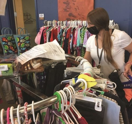 A woman wearing a medical mask shopping at a thriftstore clothing rack.