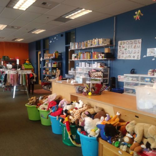 Interior photo of Wellspring's Family Store checkout counter with tubs of toys in front and racks of clothing in the back.