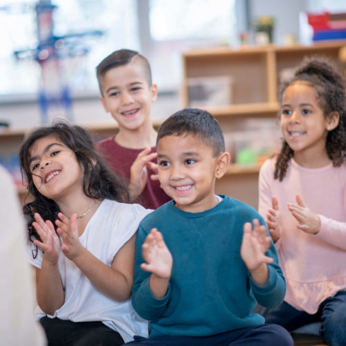 Children clapping and singing in a classroom.