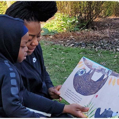 Mother and child read book outside.