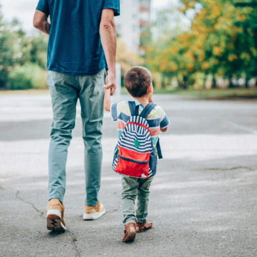 Adult holding hands with child walking down the street wearing a backpack.